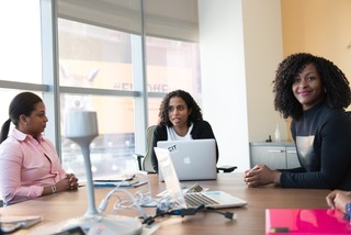Three women sitting at a conference table with their laptops