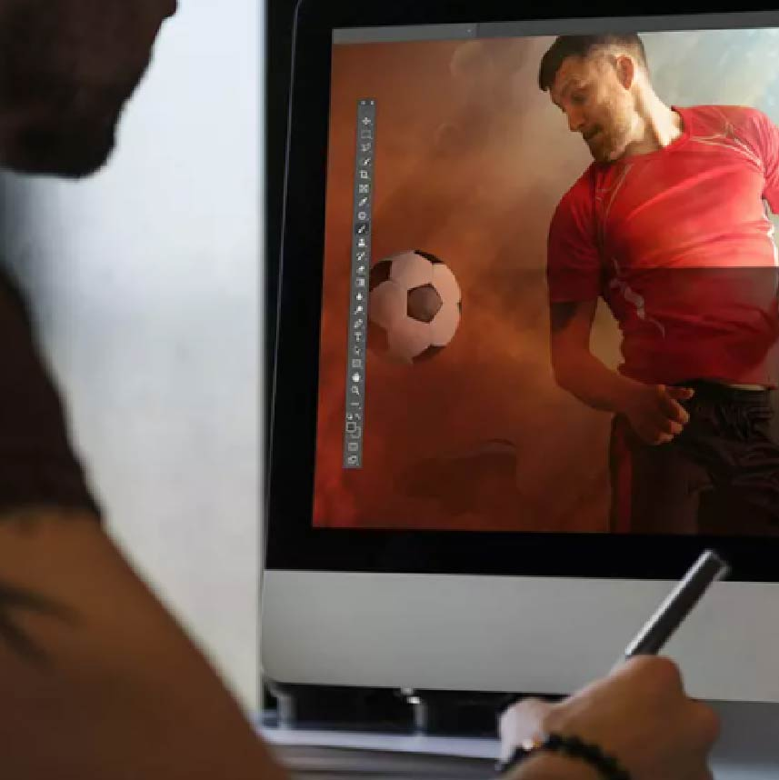 An individual looking at an image of a soccer player on the computer screen
