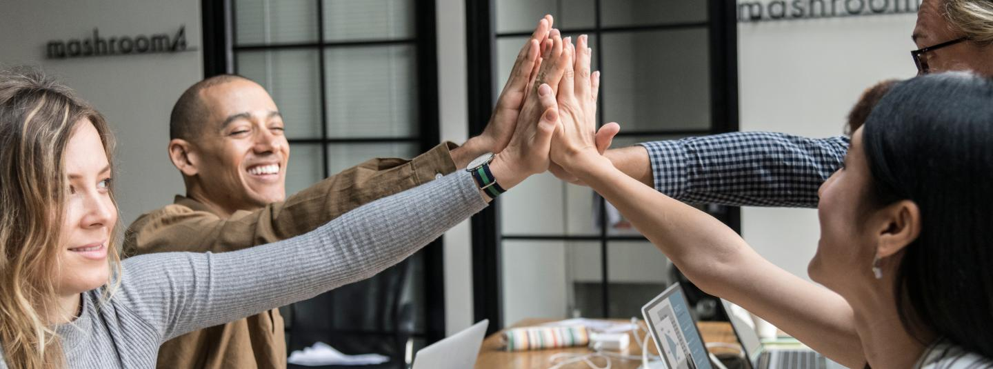 Employees high-fiving at a meeting