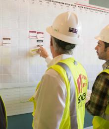 Construction workers in hard hats working on a whiteboard