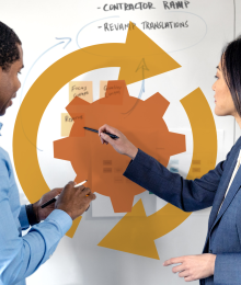 A woman and a man pointing to a white board with diagrams on it