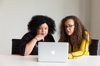 Two women looking at a Macbook