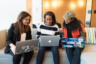 Three women huddling together on a couch with their laptops