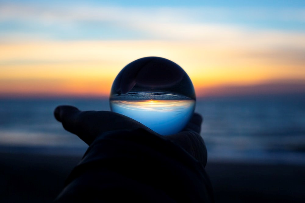 A hand holding up a clear glass globe against the backdrop of the ocean
