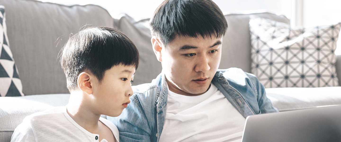 Father and Son working in front of a laptop